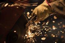 Металеві працівник, використовуючи точильної верстата у майстер-клас фабриці — стокове фото