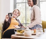 Pregnant young woman showing ultrasound scan to friend in a cafe — Stock Photo