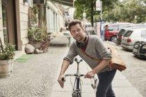 Homme à vélo dans la rue de la ville — Photo de stock