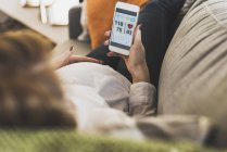 Pregnant woman on couch using smartphone checking health data — Stock Photo