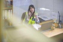 Женщина-инженер-строитель звонит в офис на стройке — стоковое фото
