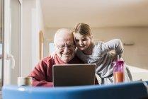 Grand-père et sa petite-fille avec battre en ordinateur portable — Photo de stock