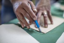 Крупный план работы портного за столом в мастерской — стоковое фото