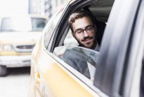 Empresário sorridente, sentado em um táxi, Nova Iorque, EUA — Fotografia de Stock