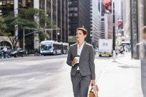 Businesswoman walking in Manhattan with takeaway coffee, USA, New York — Stock Photo