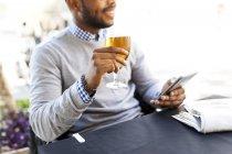 Jovem com smartphone, beber uma cerveja no café de rua — Fotografia de Stock
