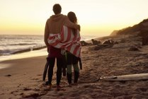 Couple embracing on the beach at sunset next to surfboard — Stock Photo