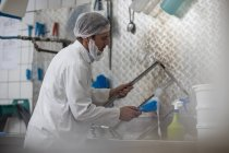 Cheese factory worker cleaning container parts — Stock Photo
