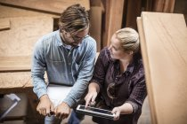 Man and woman working together in woodwork — Stock Photo