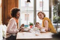 Deux jeunes femmes avec téléphone portable rencontre dans un café — Photo de stock