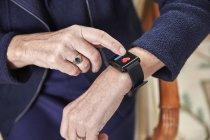 Senior woman checking medical data on smartwatch — Stock Photo