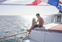 Jeune couple lors d'un voyage de bateau assis sur le pont — Photo de stock
