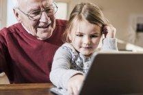 Grand-père et petite-fille utilisant ordinateur portable ensemble — Photo de stock