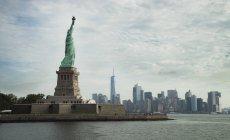 USA, New York City, statua della libertà su Liberty Island e skyline su priorità bassa — Foto stock
