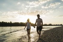 Couple walking hand in hand at the riverside at sunset — Stock Photo