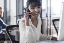 Young woman on the phone, working in office — Stock Photo
