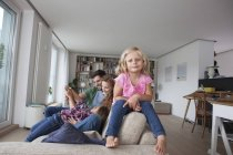 Портрет маленькой девочки, сидящей на спинке дивана со своей семьей на заднем плане — стоковое фото