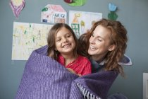 Portrait of happy mother and little daughter together in children's room — Stock Photo