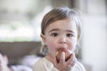 Bébé fille manger pomme et regarder caméra — Photo de stock
