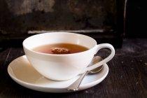 Vista del primo piano del tè nero in tazza di porcellana bianca — Foto stock