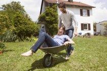 Playful caucasian couple with wheelbarrow in garden — Stock Photo