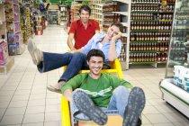 Троє друзів, які мають задоволення разом в супермаркеті — стокове фото