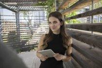 Mulher jovem sorridente permanente com tablet digital na pérgula — Fotografia de Stock