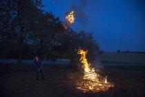 Niño en el fuego del campamento en un prado por la noche - foto de stock
