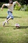Мальчик играет в футбол в саду — стоковое фото