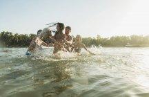 Щасливі друзі грати з м'ячем у воді — стокове фото