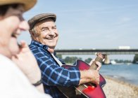 Germany, Ludwigshafen, portrait of laughing senior man with guitar at riverside — Stock Photo
