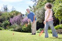 Kleines Mädchen spielt Badminton mit ihrem Großvater — Stockfoto