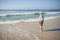Spain, Ferrol, senior woman standing on the beach looking at distance — Stock Photo