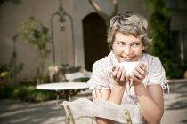 Ritratto di donna matura sorridente che si siede nel giardino con la tazza di Cappuccino — Foto stock
