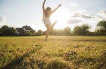 Задний вид женщины, прыгающей в воздух на лугу при подсветке — стоковое фото