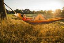 Donna che si rilassa in un hammock mentre usando il computer portatile — Foto stock