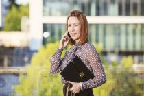 Portrait of redheaded businesswoman holding file telephoning with smartphone — Stock Photo