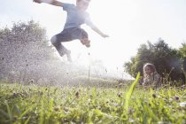 Caucasian boy and girl splashing with water in garden — Stock Photo