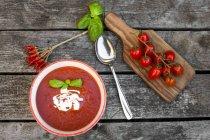 Bol de soupe de tomate maison sur bois — Photo de stock