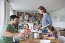 Paar mit zwei Kindern isst zu Hause gemeinsam zu Mittag — Stockfoto