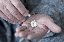 Mãos de homem sênior segurando comprimidos — Fotografia de Stock