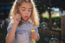 Little girl blowing soap bubbles — Stock Photo