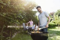 Caucasian family having a barbecue in garden — Stock Photo