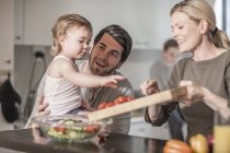 Family in kitchen preparing food together — Stock Photo