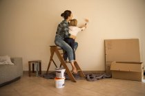 Mother and daughter painting a wall in new apartment — Stock Photo
