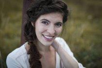 Улыбающаяся женщина с косой, смотрящая в камеру — стоковое фото