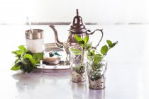 Tray with tea pot, sugar, mint leaves and glasses — Stock Photo