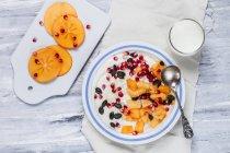 Dish of natural yoghurt, kaki, pomegranate seed, almond and pumpkin seed — Stock Photo