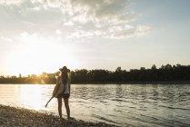 Jeune femme avec la guitare sur le bord de la rivière à la recherche au coucher du soleil — Photo de stock