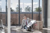 Businessman sitting on the floor in a new office — Stock Photo